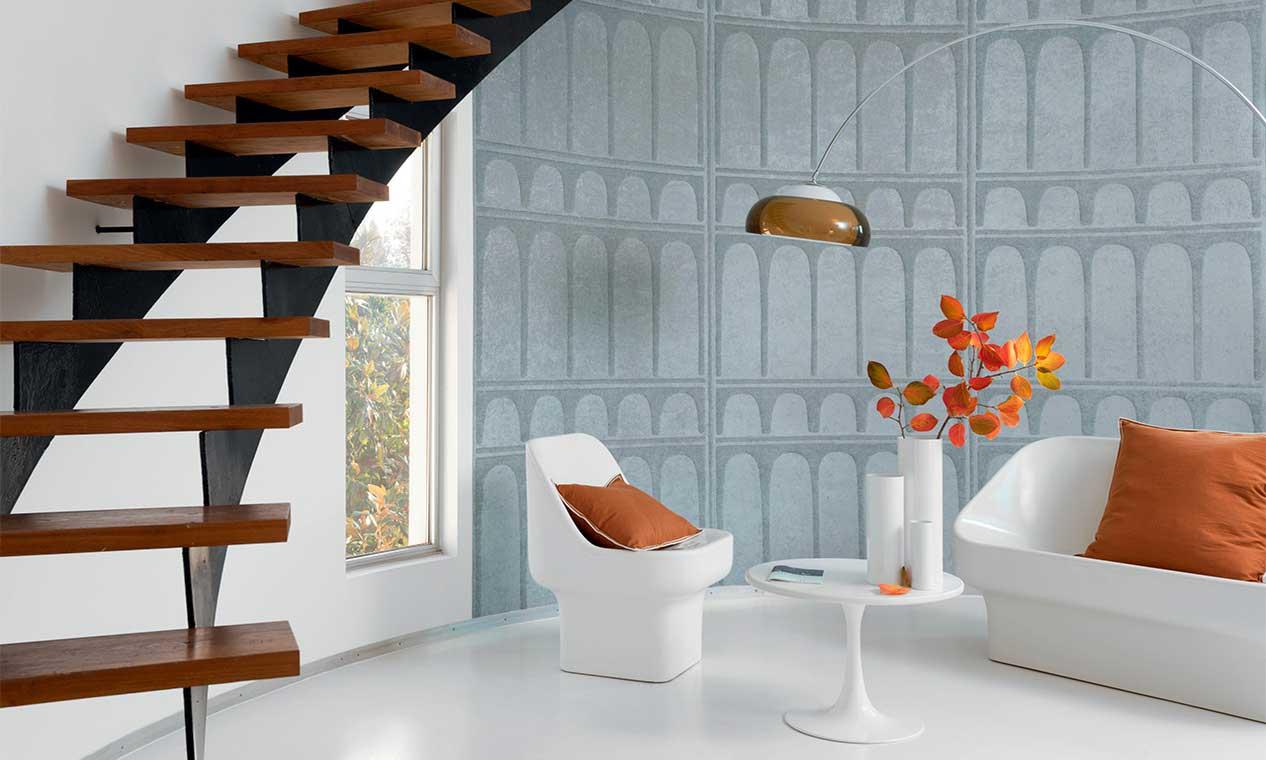 Un salon à l'ambiance méditerranéenne avec une tapisserie textile grise ornée de colonnes en relief