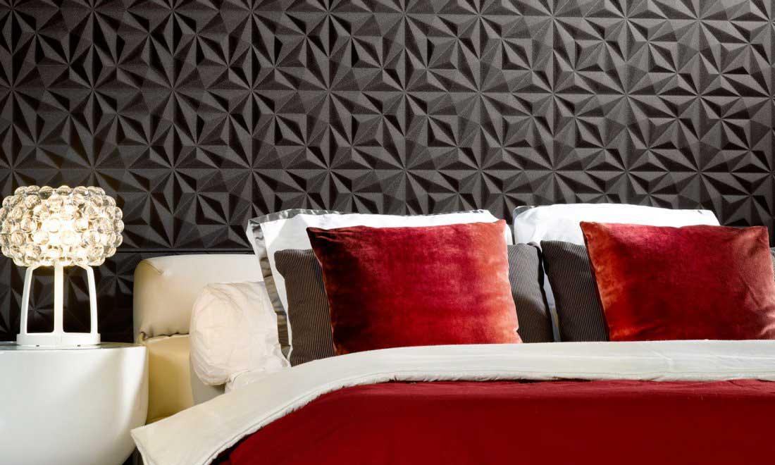 Une chambre parée de linge de lit gris, blanc et rouge esthétique avec une tête de lit texturée en relief sombre