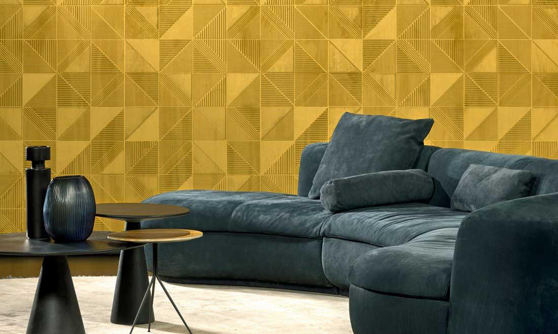 Un salon coloré au revêtement mural en relief géométrique jaune et un grand canapé bleu effet velours
