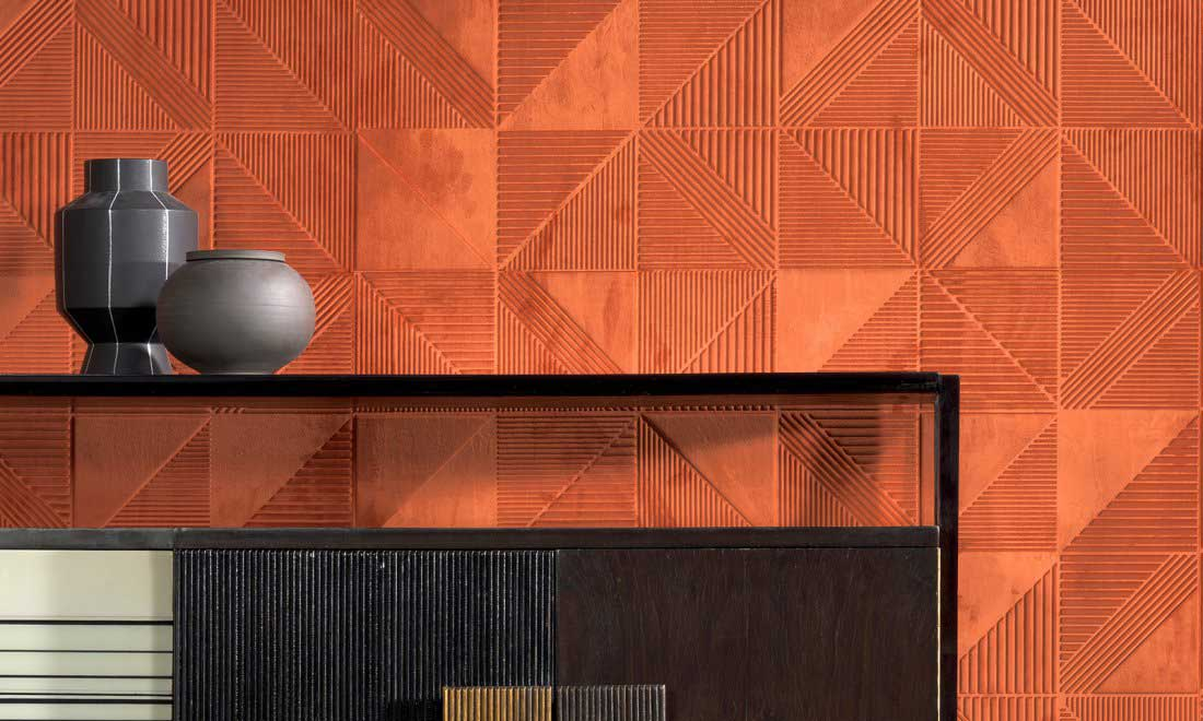 Un revêtement mural géométrique rouge en relief derrière une étagère noire avec des pots décoratifs