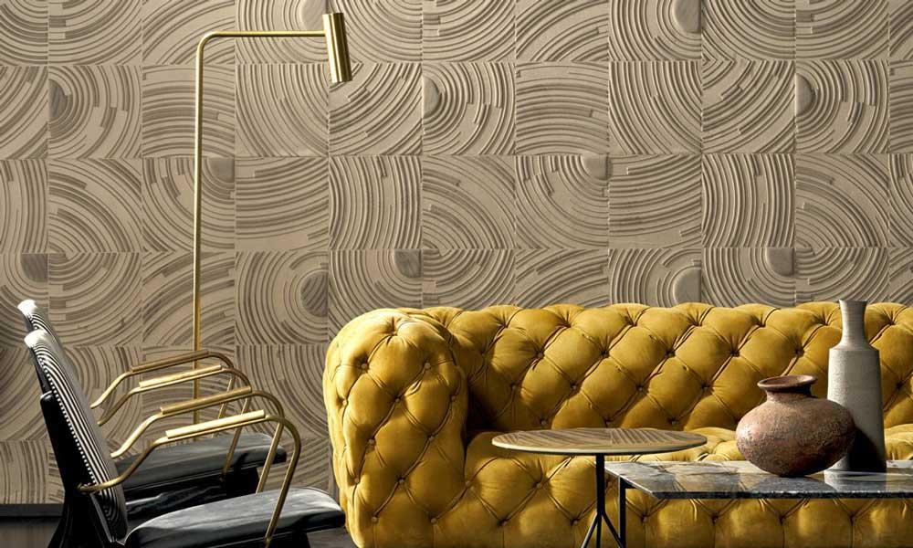 Un revêtement textile dans un salon qui rappelle les rides de sable sur les plages derrière un canapé matelassé jaune