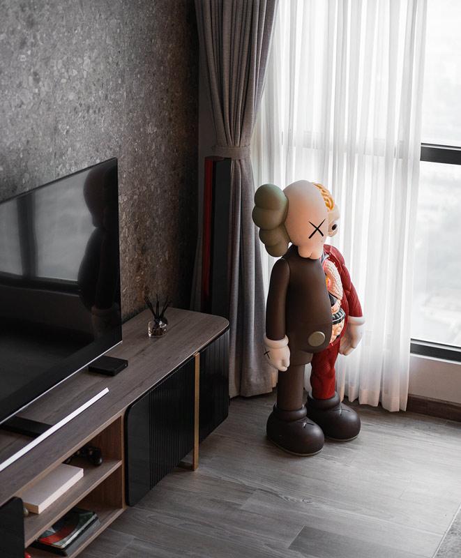 Un salon contemporain avec un mur en Terrazzo noir et un art toys géant coloré